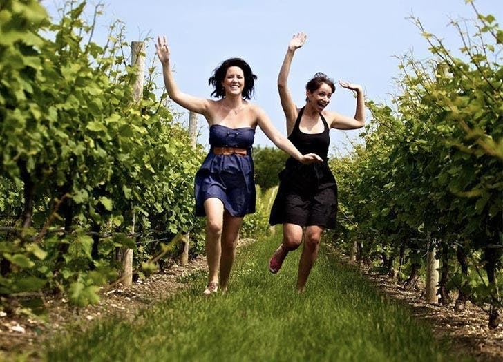 two girls running through winery