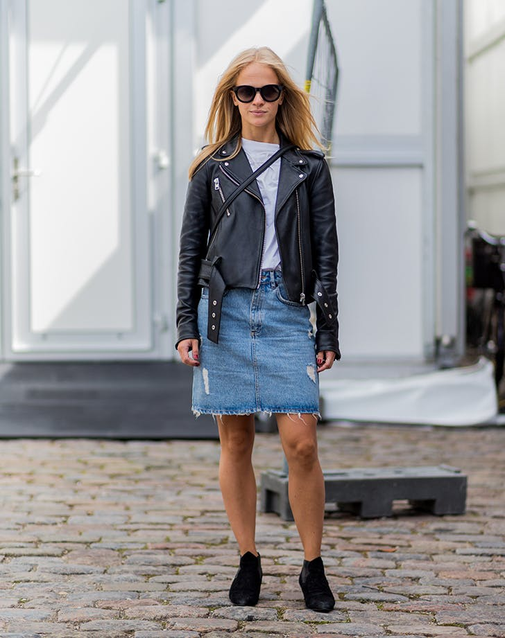 woman wearing a jean skirt and moto jacket
