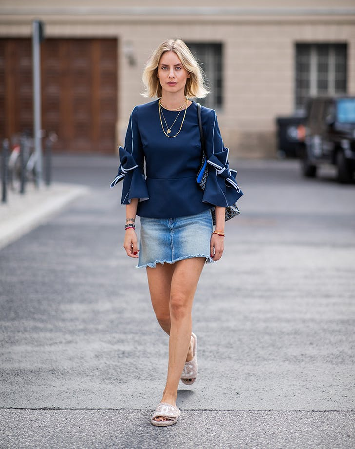 woman wearing a statement top and jean skirt