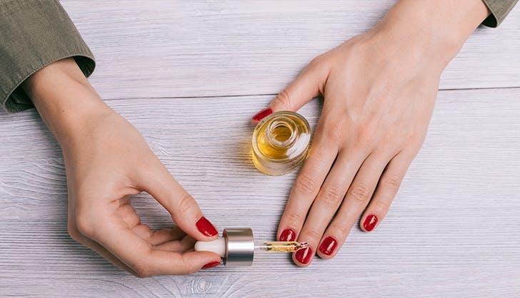 woman applying cuticle oil