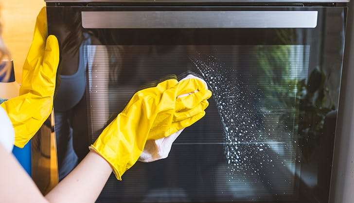woman cleaning stove with gloves on
