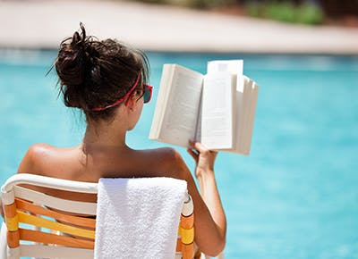 woman reading book by pool 400