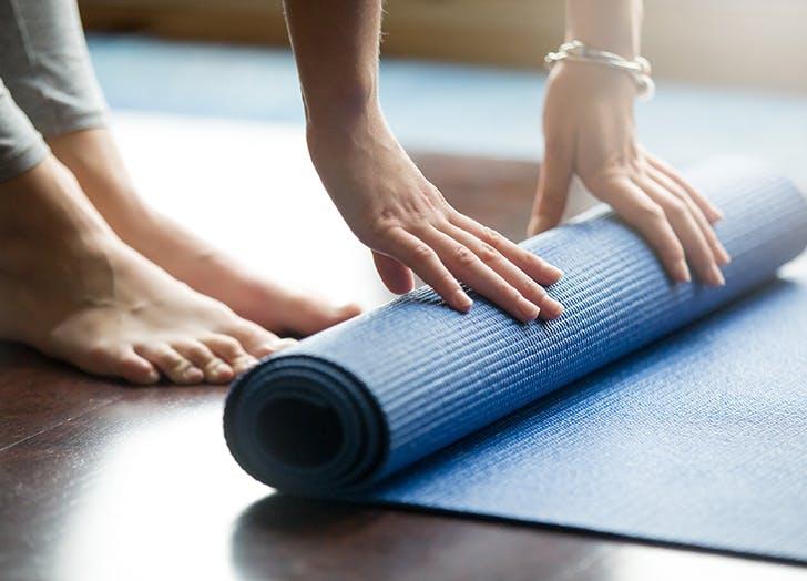woman unrolling yoga mat