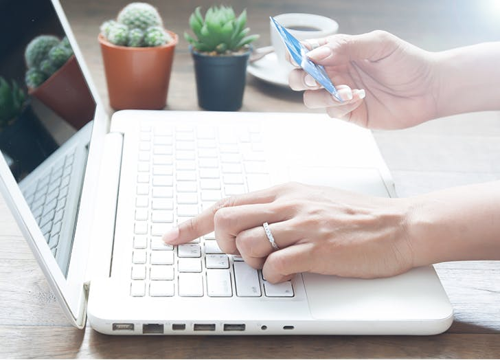 woman using credit card on computer