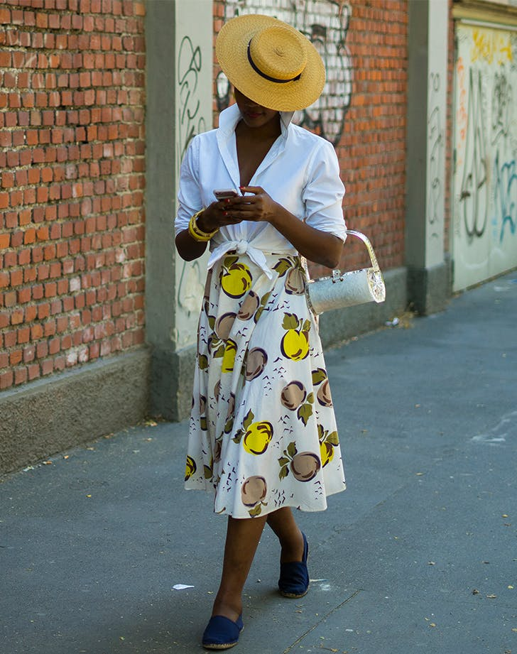 woman wearing a straw boater hat and lemon skirt