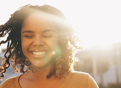 woman with curly hair smiling 400