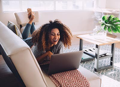 Woman watching Netflix on computer at home 400