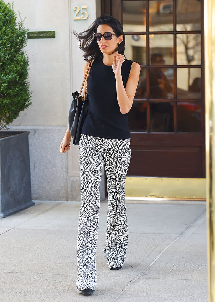 amal clooney wearing a black top and printed bell bottoms