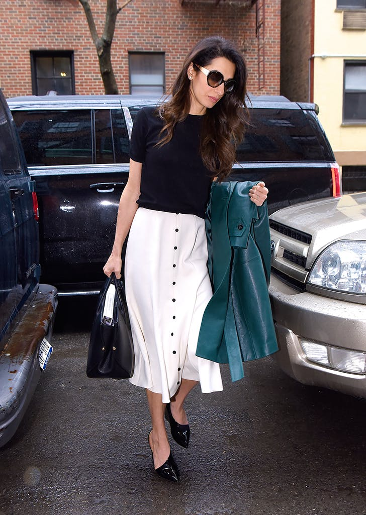 amal clooney wearing a black top and white skirt