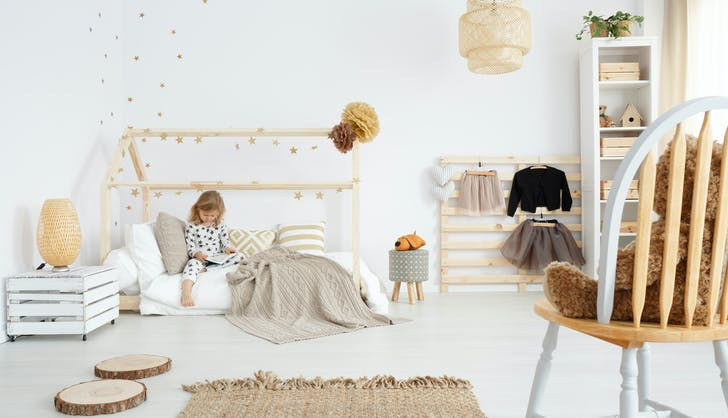 little girl sitting on her bed with clothes laid out nearby