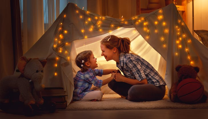 mom and daughter playing indoor camping with a tent fort
