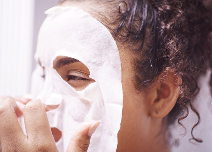 woman putting facemask on
