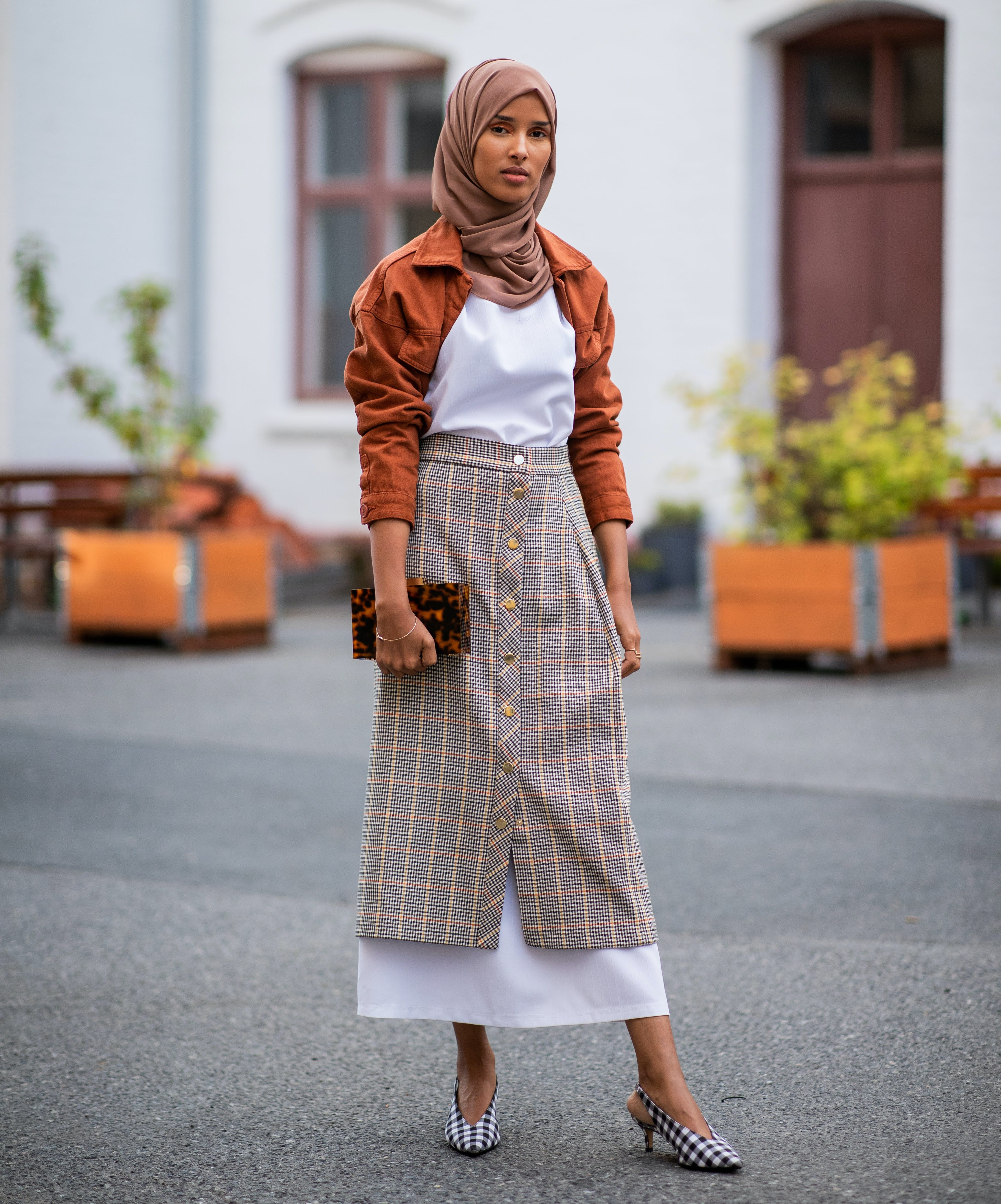 woman wearing a burnt orange jacket plaid skirt and gingham shoes