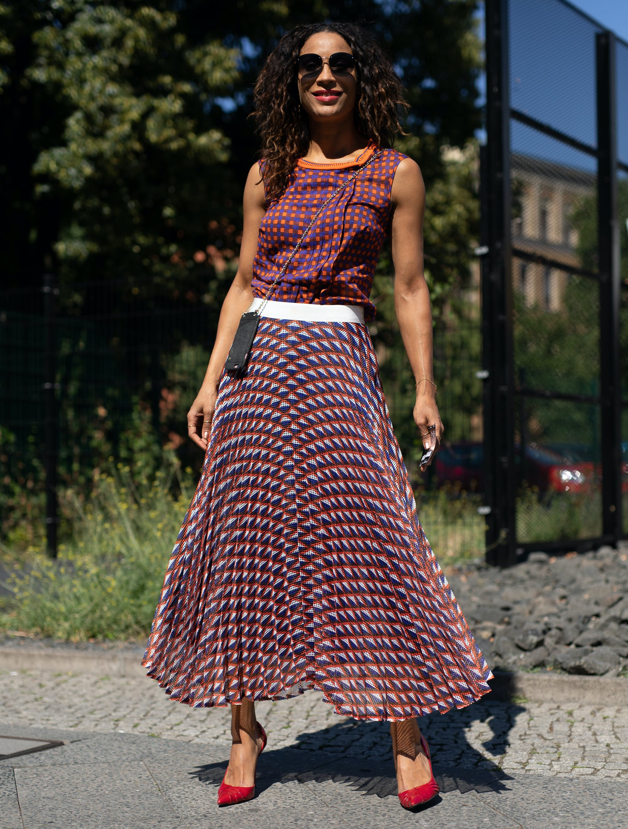 woman wearing a sweater shell and pleated midi skirt