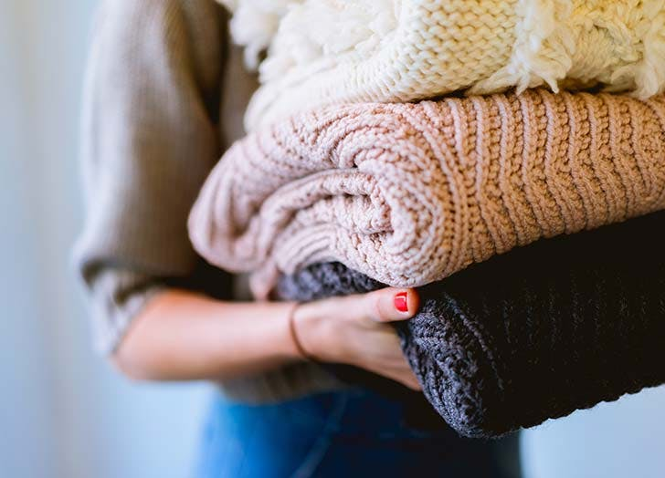 woman with folded sweaters