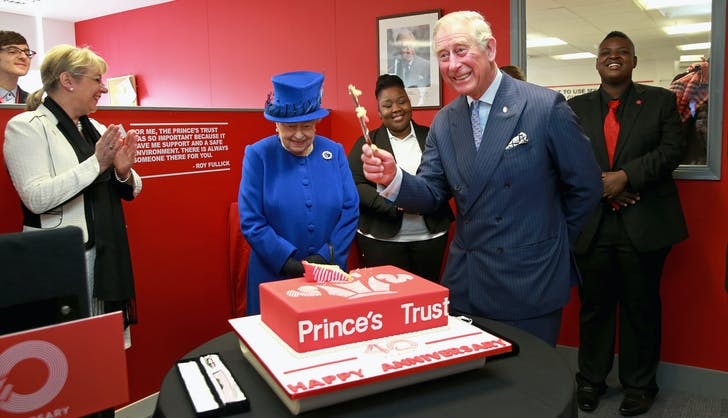 Prince Charles cuts cake while Queen Elizabeth watches