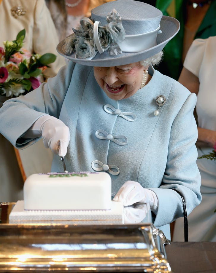 Queen Elizabeth gleefully cuts cake
