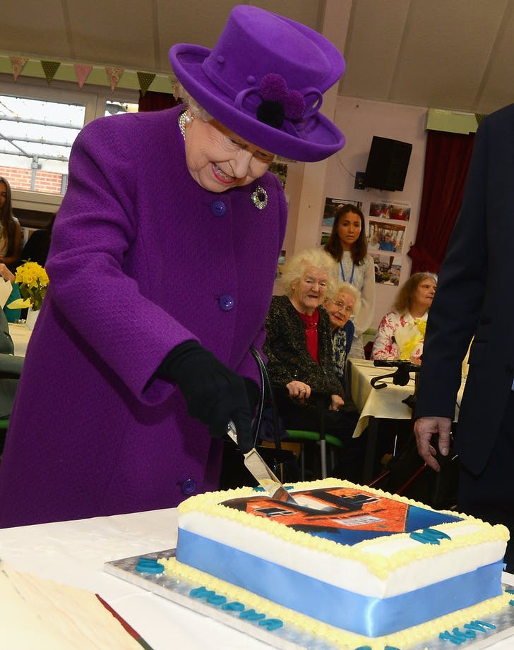 Queen Elizabeth smiles while cutting cake
