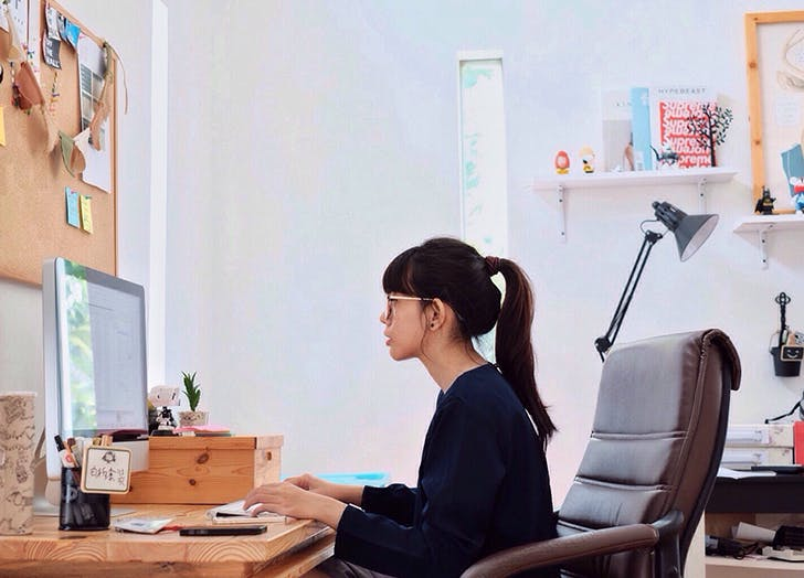 woman sitting at a desk in front of a computer