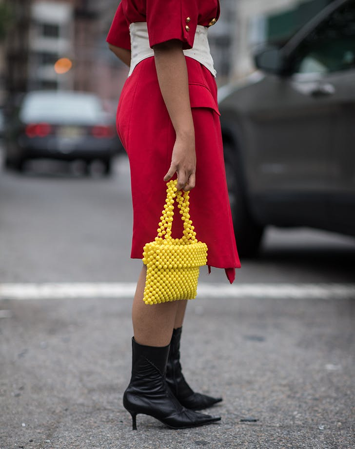woman wearing a red dress and beaded bag