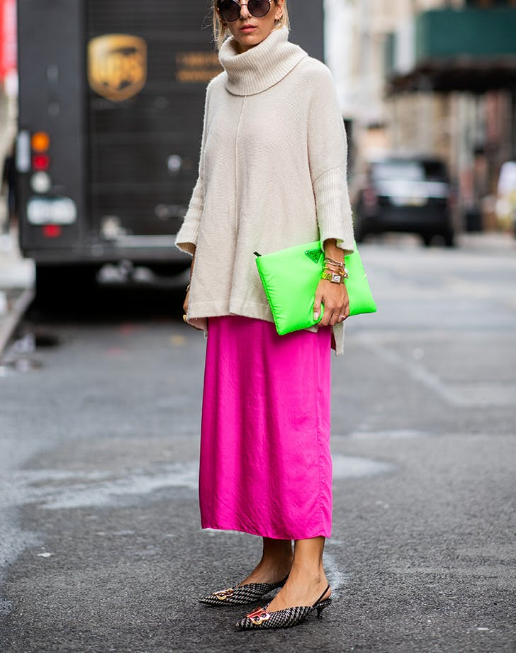 woman wearing a sweater and neon pink skirt