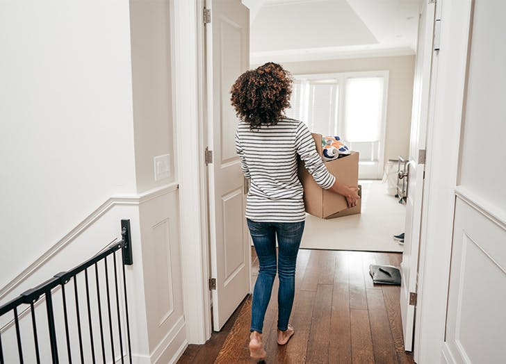 woman carrying a box in her home