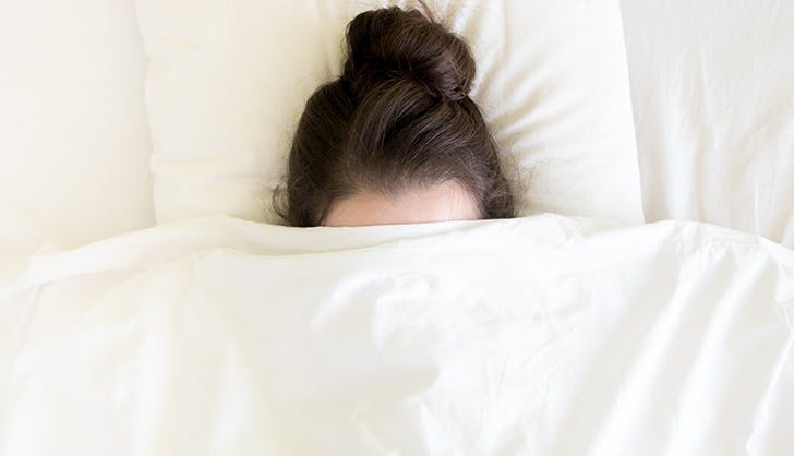woman hiding under the covers to destress