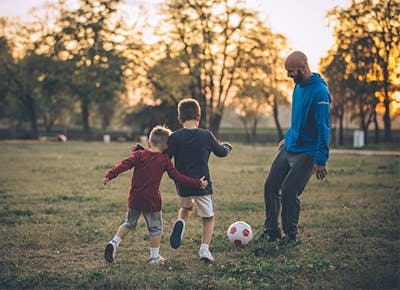 guy playing Soccer with kids 400
