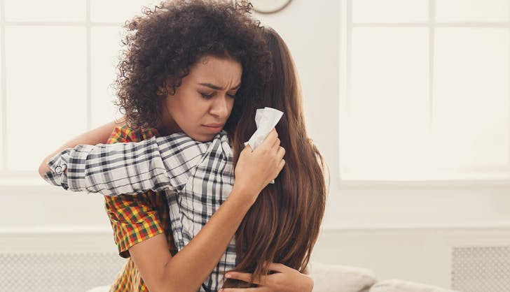 two stressed women hugging