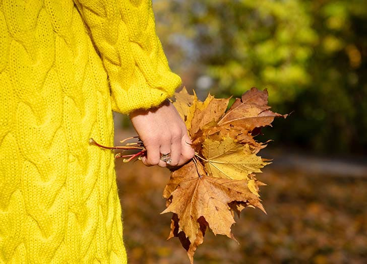 woman in yellow jacket holding leaves