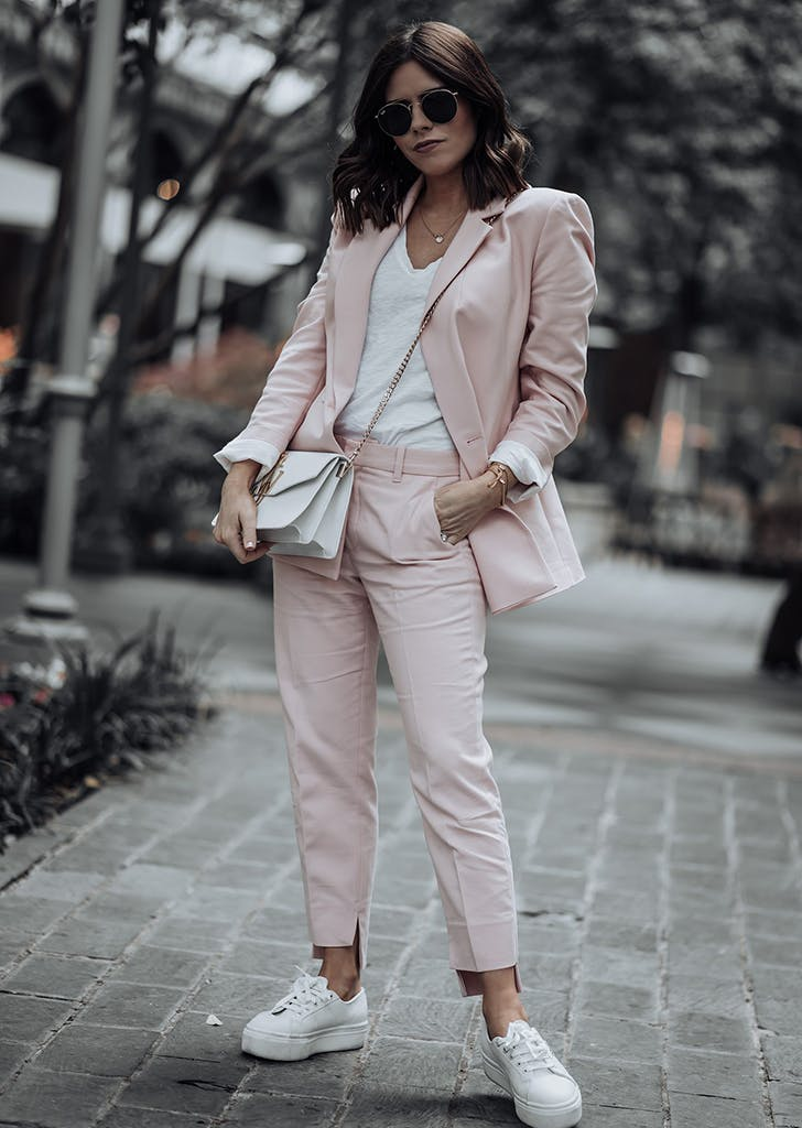 woman wearing a light pink pantsuit and sneakers
