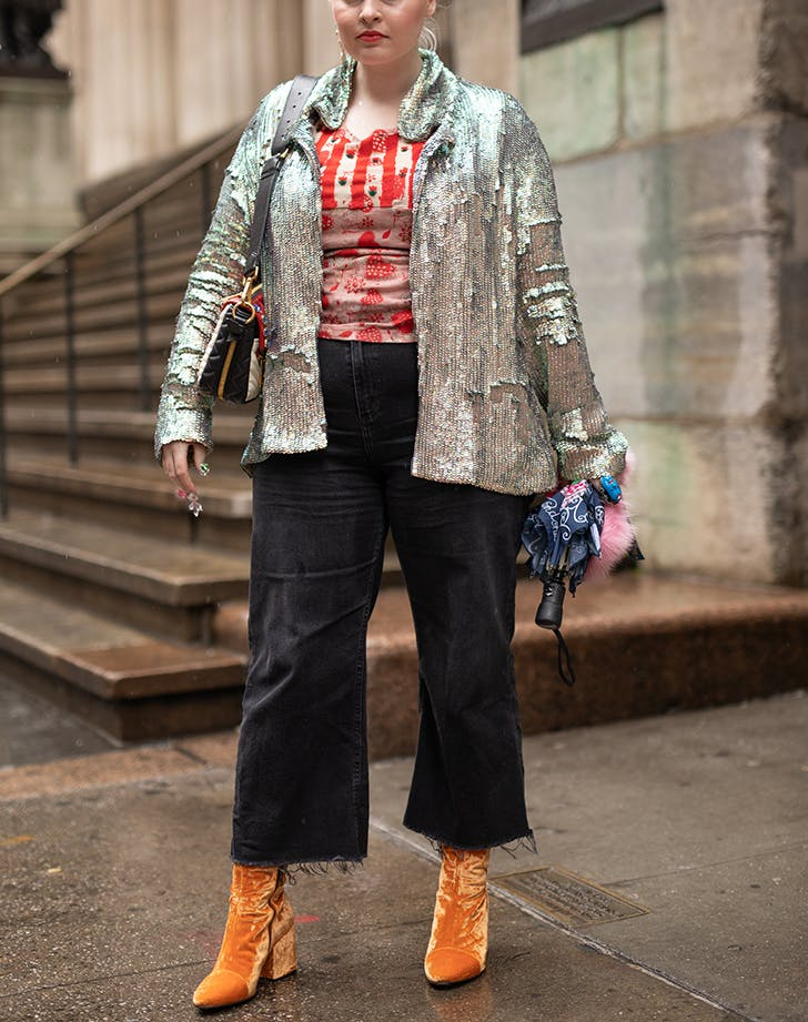woman wearing jeans a silver jacket and velvet boots
