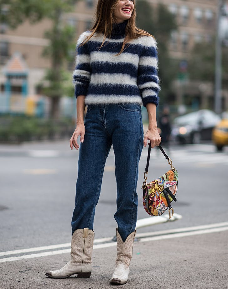 woman wearing jeans a sweater and cowboy boots