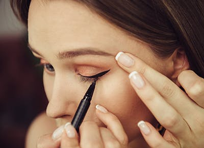woman applying eyeliner 400