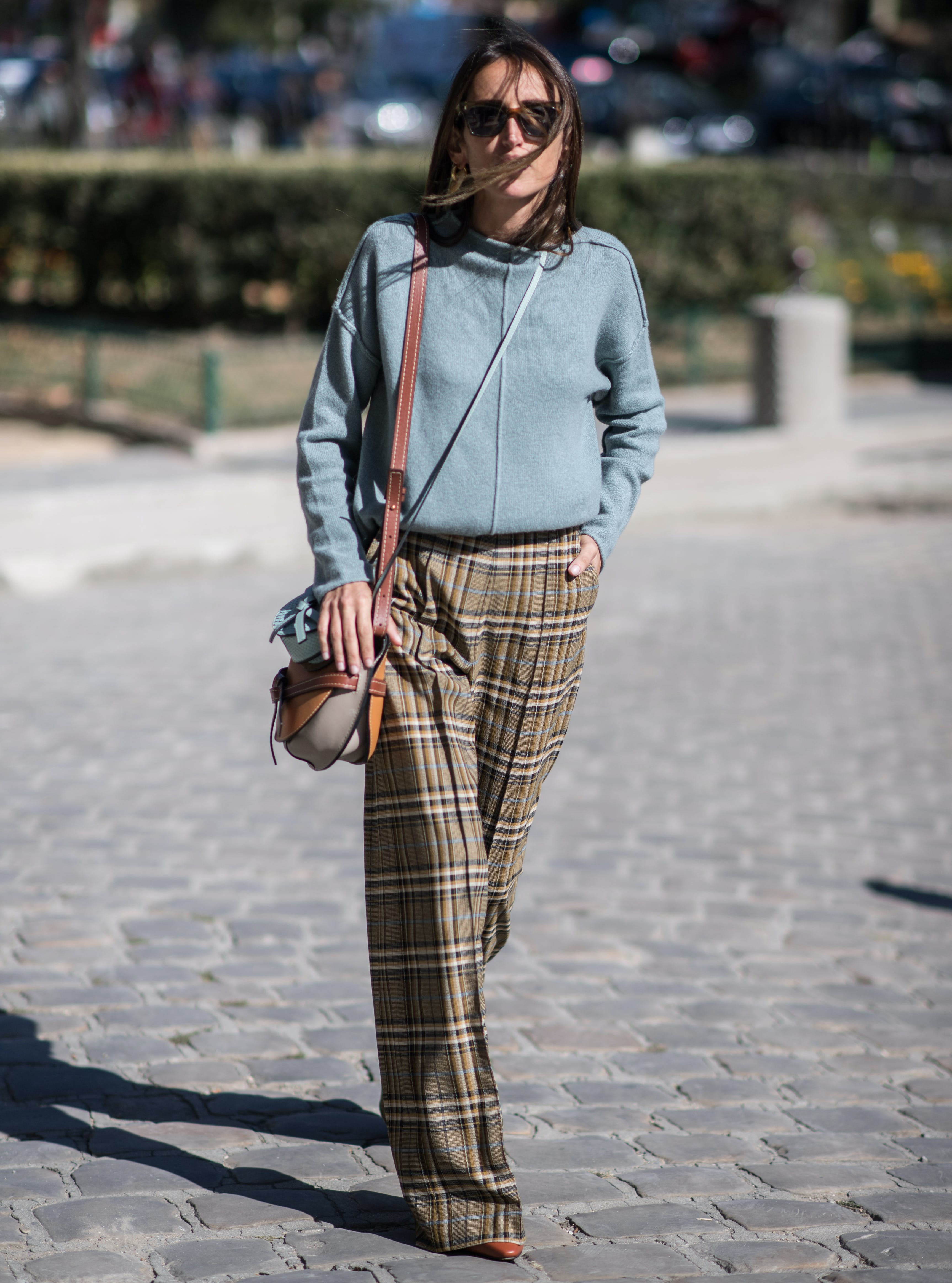 woman wearing a sweatshirt and plaid trousers