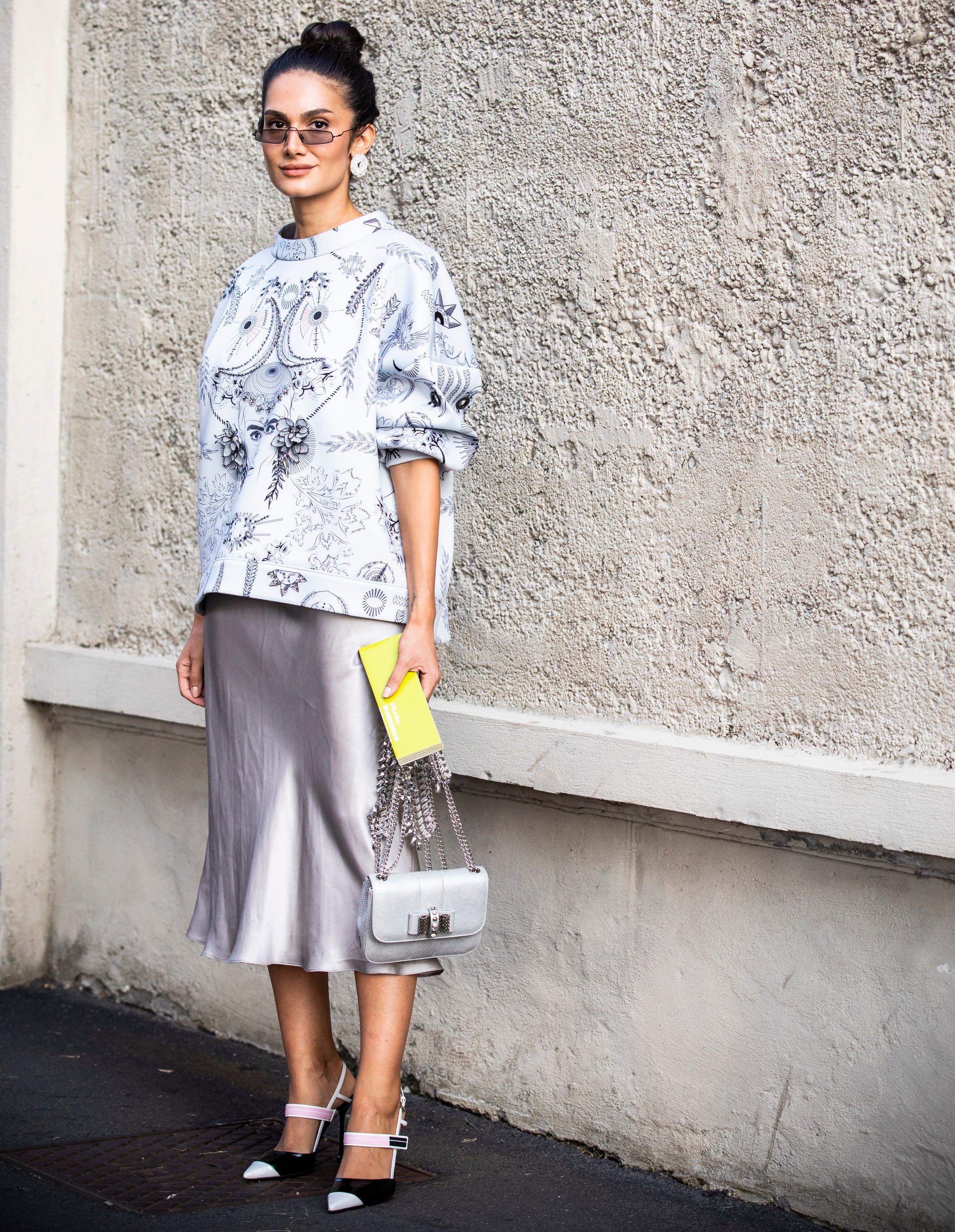 woman wearing satin skirt and sweatshirt with heels