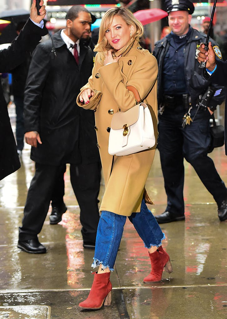 kate hudson wearing a camel coat jeans and red boots