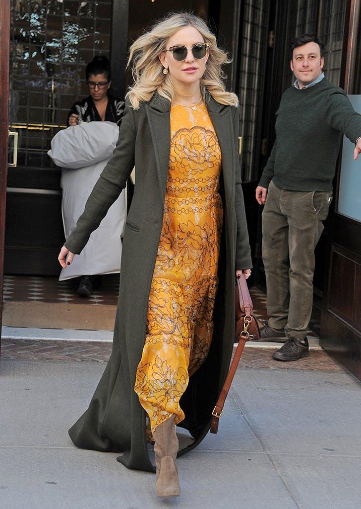 kate hudson wearing an orange maxi dress and olive coat