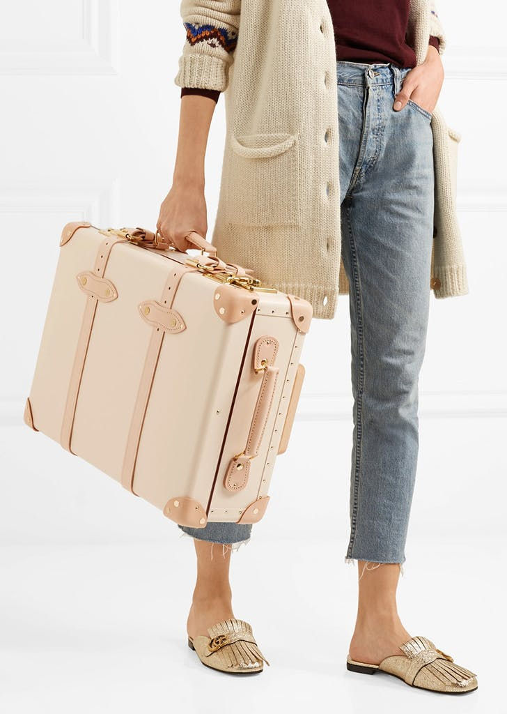 woman holding a light pink globe trotter suitcase