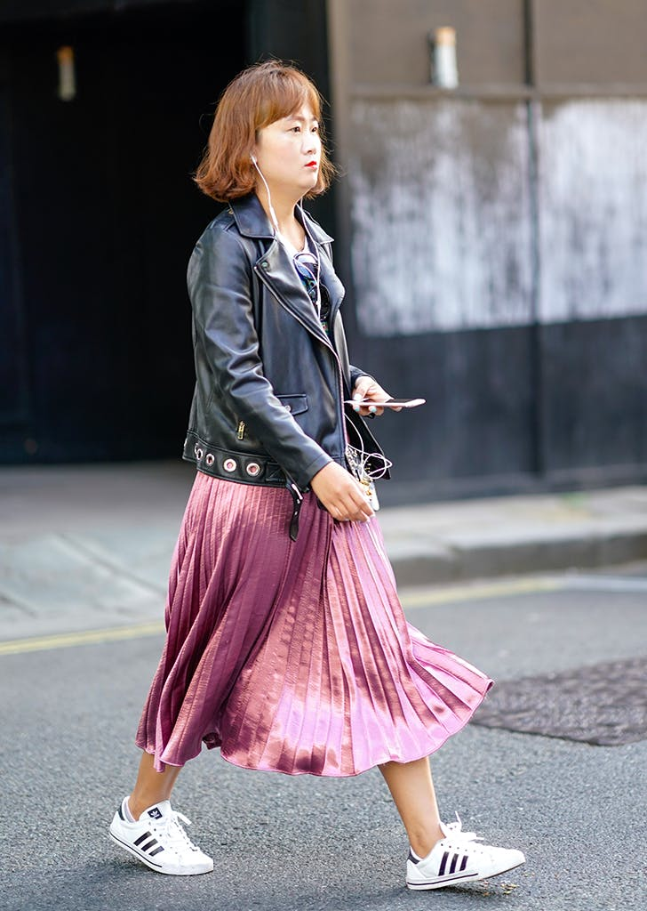 woman wearing a pleated skirt and moto jacket