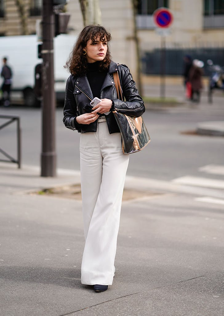 woman wearing flared pants and a moto jacket