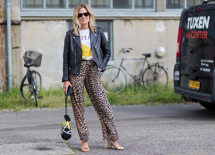 woman wearing leopard pants and a moto jacket