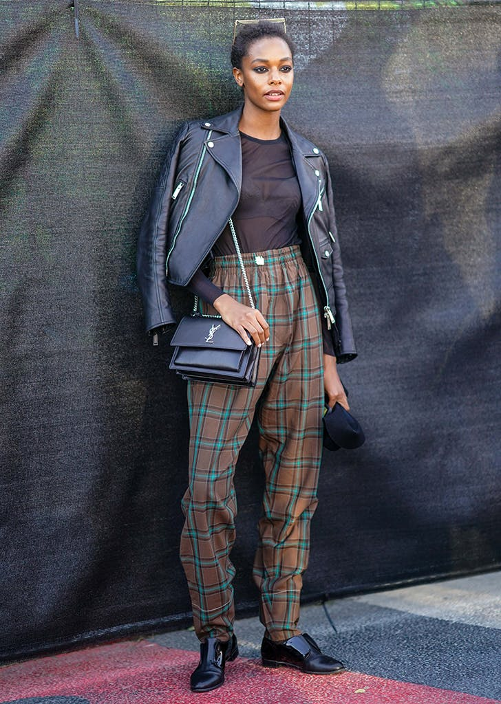 woman wearing plaid pants and a moto jacket