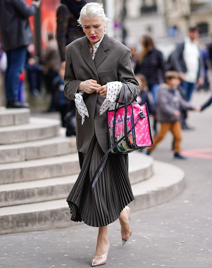 woman wearing a gray skirt suit and carrying a pink bag