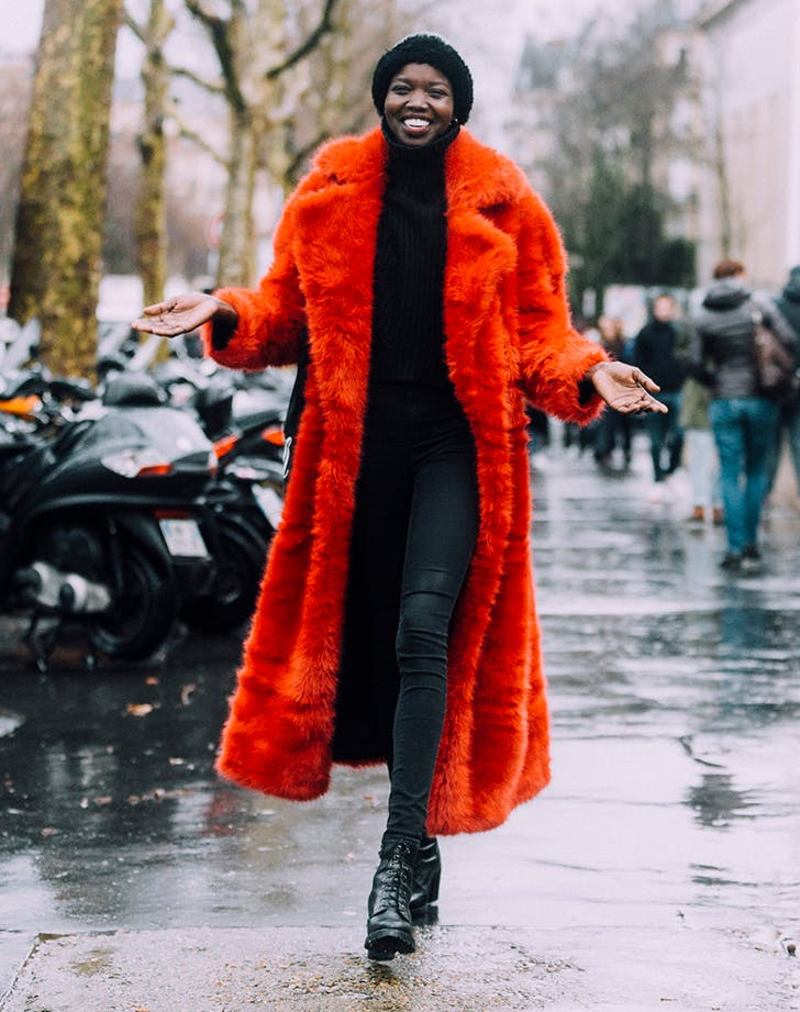 woman wearing a red faux fur coat