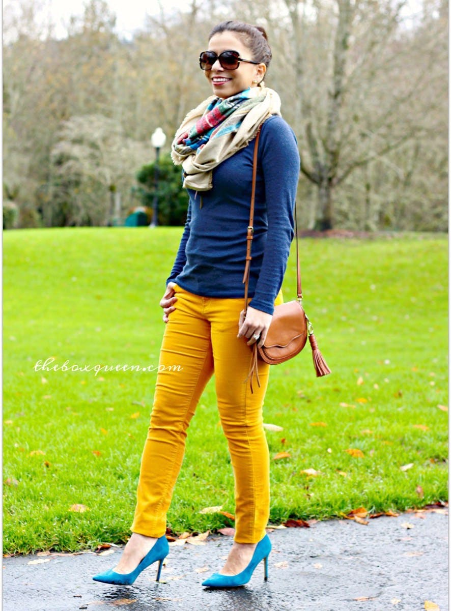 woman wearing marigold corduroy pants and navy sweater and bright heels