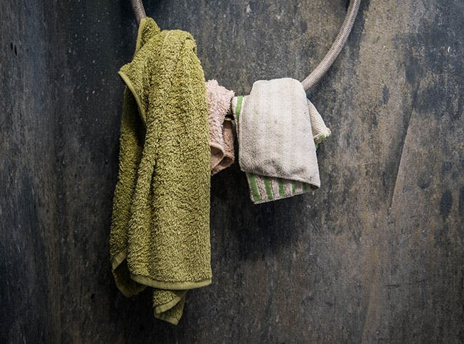 Hanging towel on shower wire with old dirty grey wall