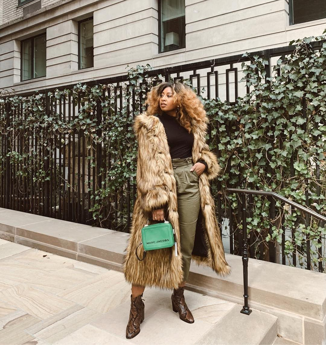 courtney danielle wearing a faux fur coat with a green bag