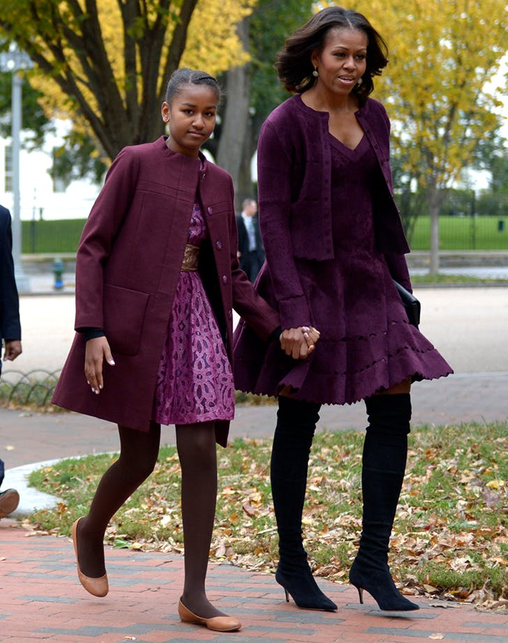 michelle obama wearing a maroon sweater and dress with over the knee boots