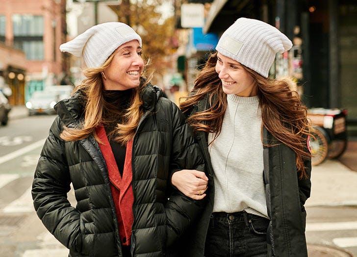 two women wearing beanies